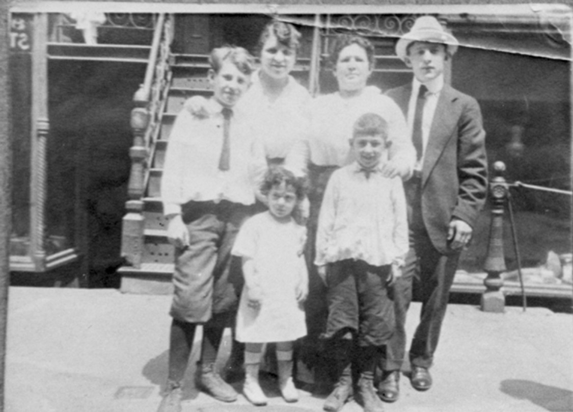 Black and white photo of the Rogarshevsky family standing in front of the steps of 97 Orchard Street