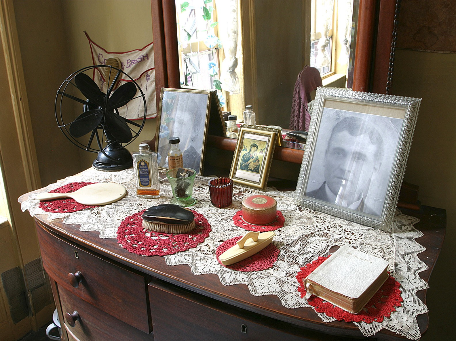 Dresser with family objects displayed in the recreated Baldizzi family parlor inside 97 Orchard Street