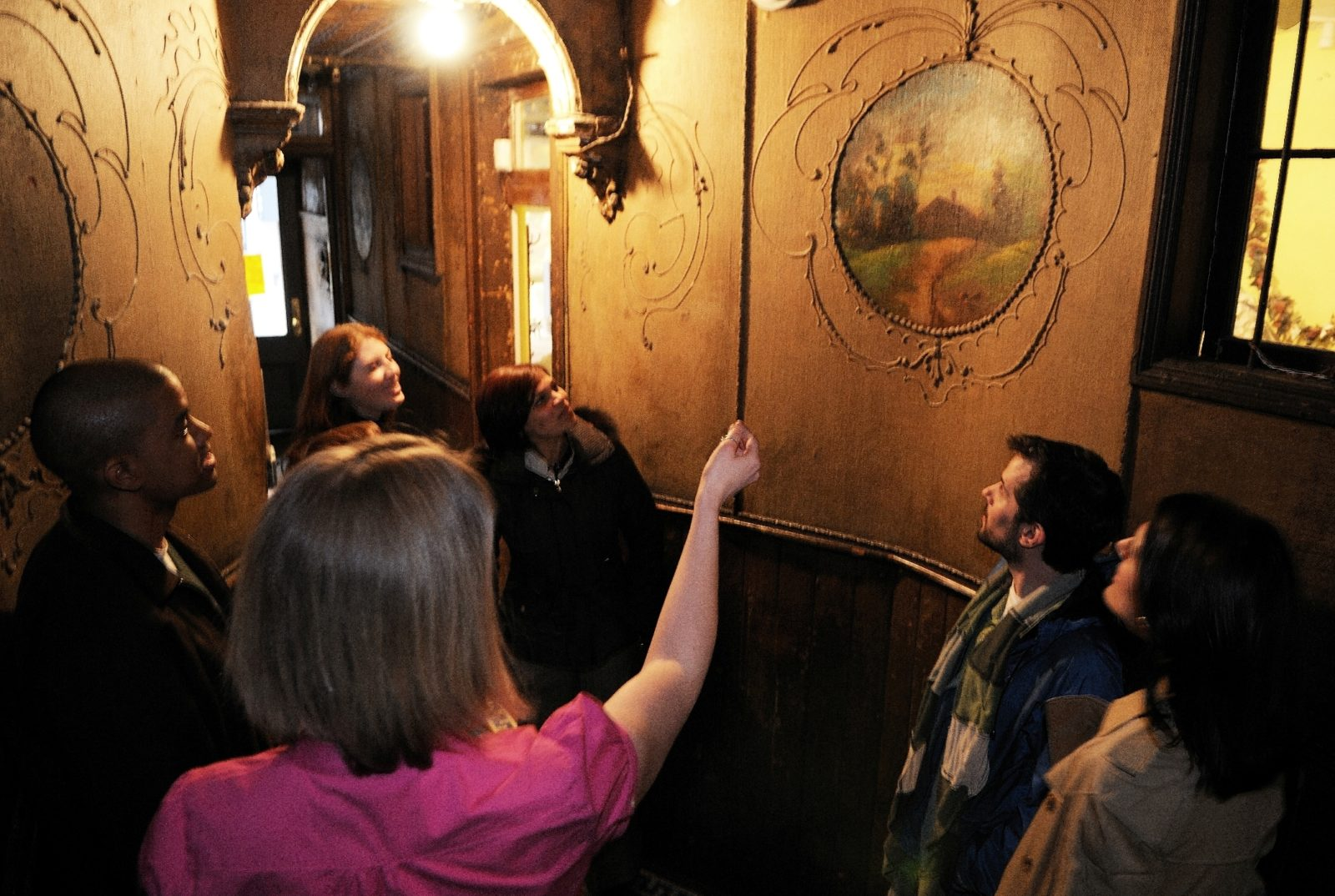 A museum educator points at a painted mural on a wall at 97 Orchard Street