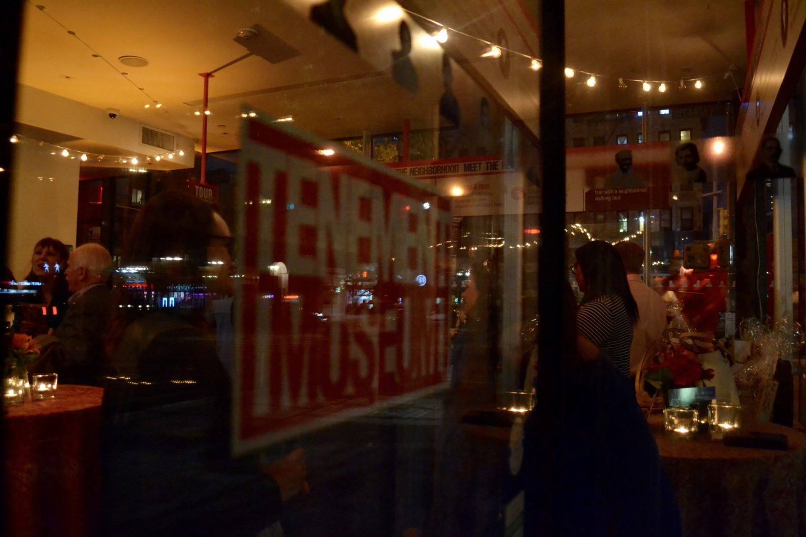 A view through the glass windows of a private event at 103 Orchard Street