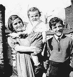 Black and white photo of a young Josephine Baldizzi carrying a baby with a young Johnny Baldizzi on the right, all smiling