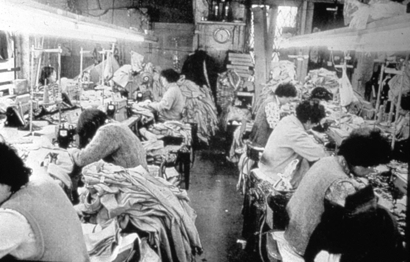 Garment factory in Chinatown where seven adults are working at sewing machine stations with overflowing piles of fabric