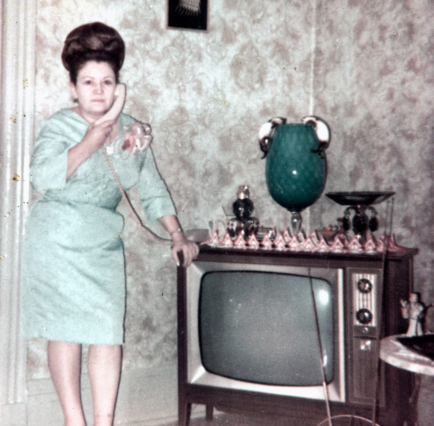 Ramonita Saez on the phone and next to the TV in her living room at 103 Orchard Street