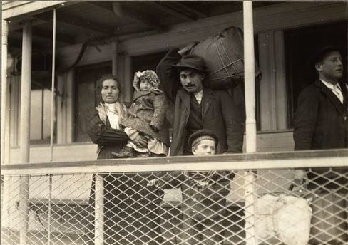 Black and white photo of a traveling family of 4, with 2 adults and 2 children, all wearing coats as one adult holds a large piece of luggage