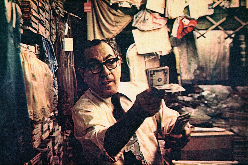 Sidney Meda holding bills of money inside his store at 97 Orchard