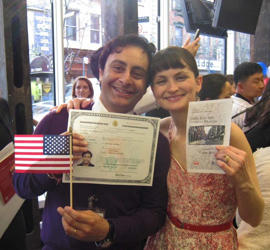 Two adults smiling, one holding a U.S. Citizenship Certificate and an American flag while the other holds a Tenement Museum pamphlet