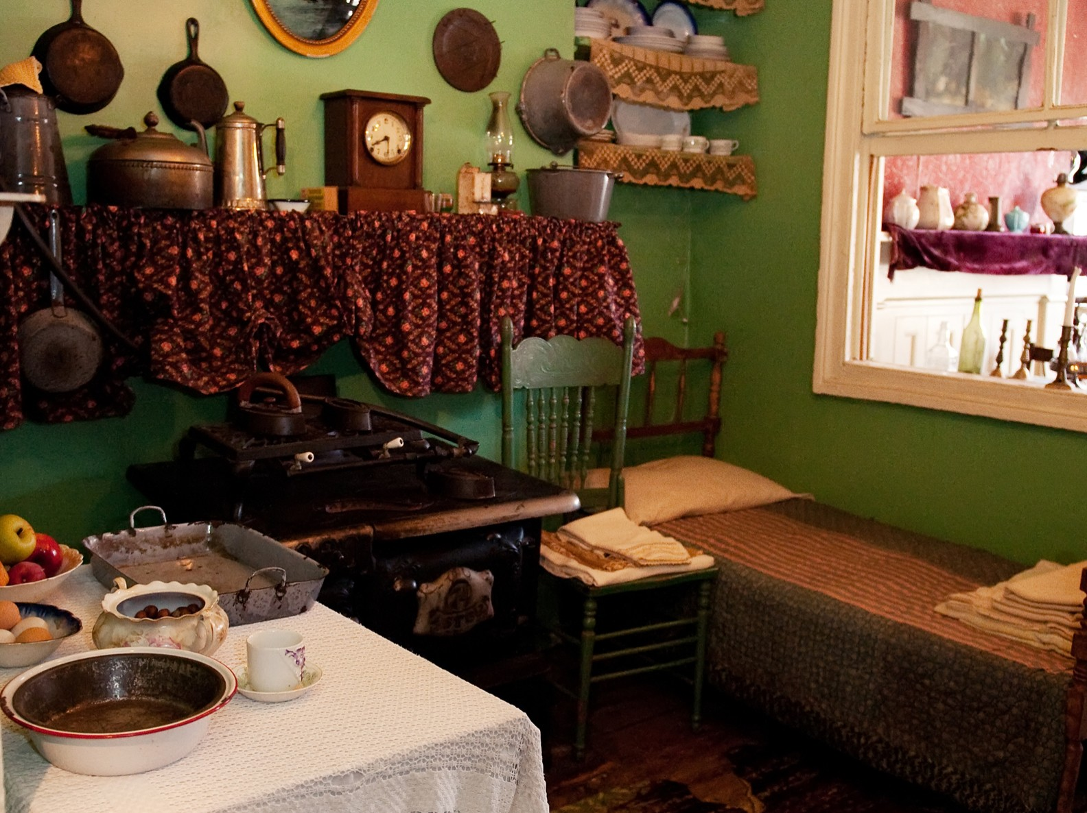 Recreated Rogarshevsky family kitchen at 97 Orchard Street where a table with food is next to a stove, a chair, and a small bed