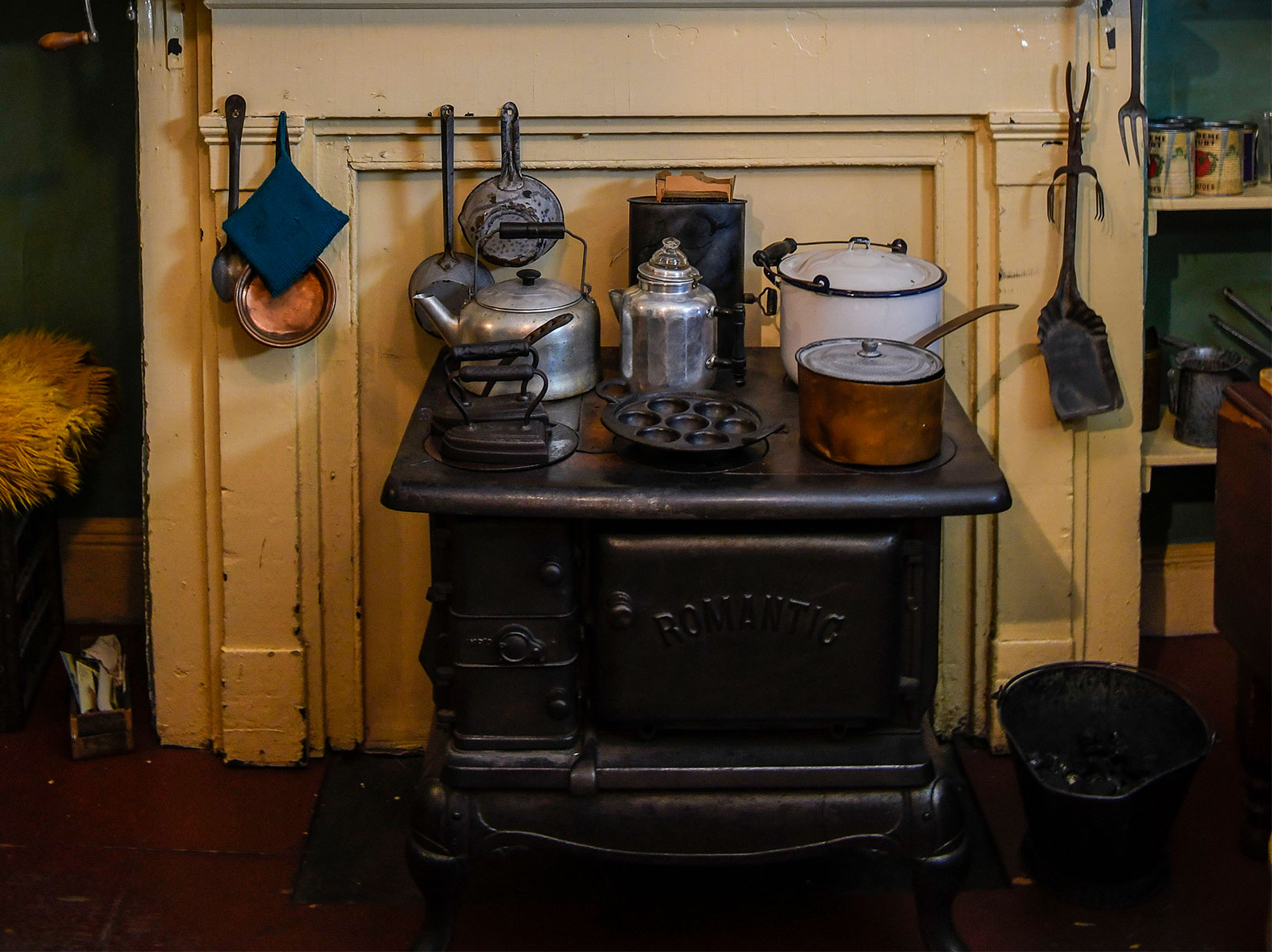 Coal stove covered with pots, kettles, and irons inside a recreated tenement apartment