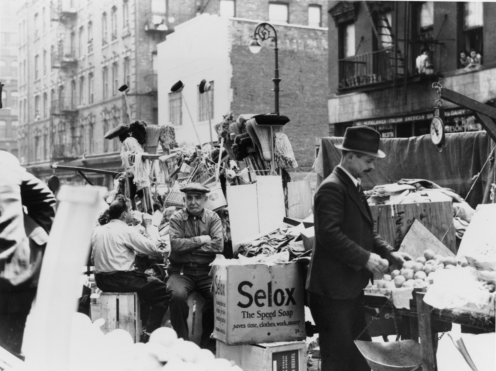 A couple of pushcarts surround a shopkeeper who is frowning while sitting on a crate with the brooms and mops they're selling piled behind them