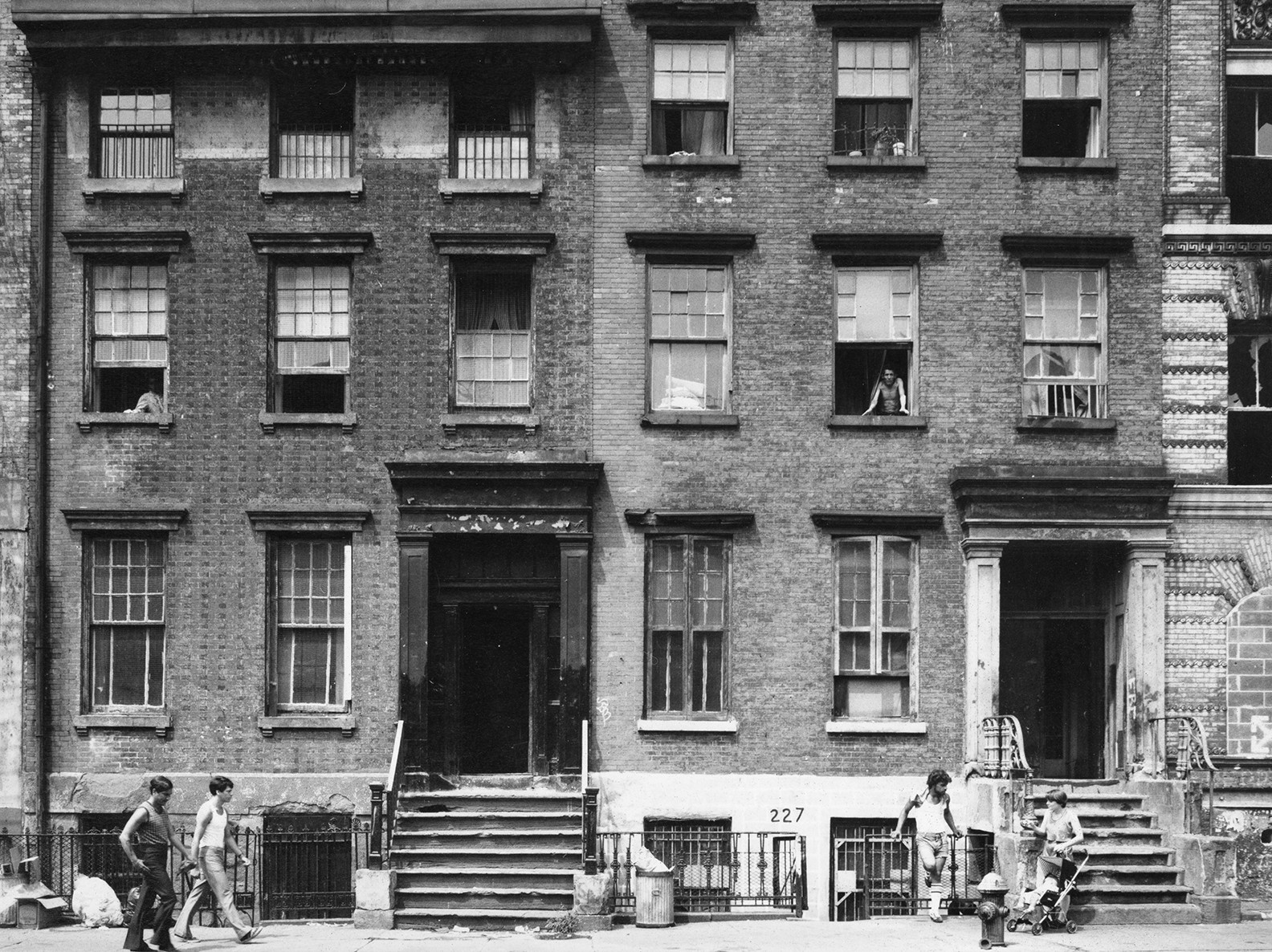 Photo of tenements with people walking by on the sidewalk, looking out from their windows, and lounging on the building steps in the summer