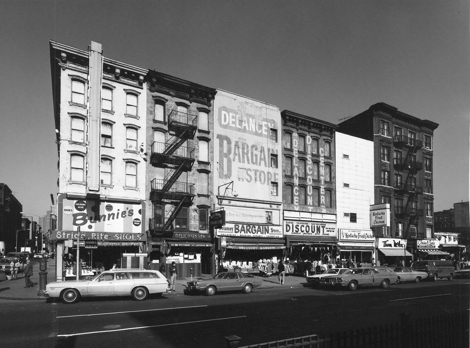 "Cars pass in front of 6 neighboring tenements with street-level storefronts for ""Delancey's Bargain Store"", ""Bunnie's Shoes"", and ""KFC"""