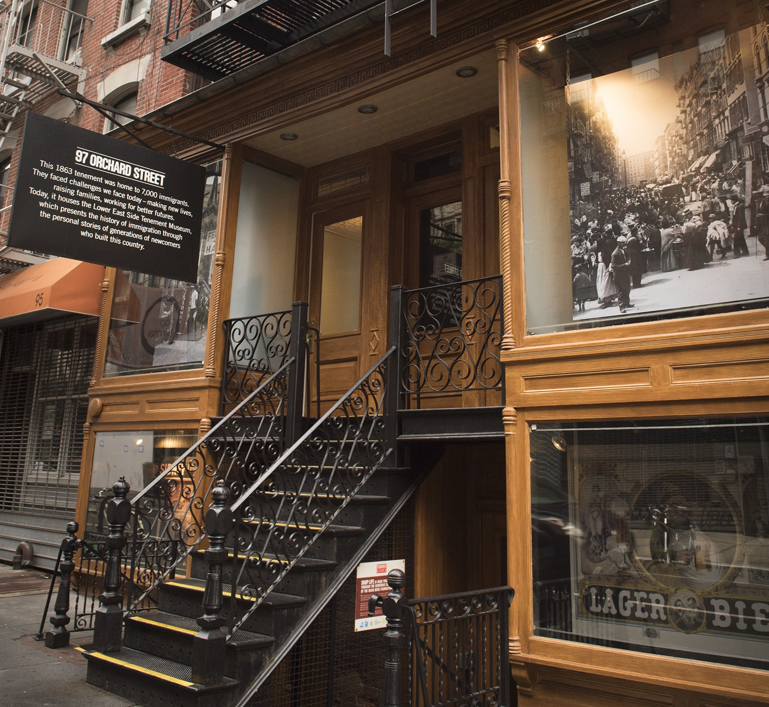 Present-day photo of the front entrance of the Tenement Museum at 97 Orchard Street with black steps leading up to wooden doors