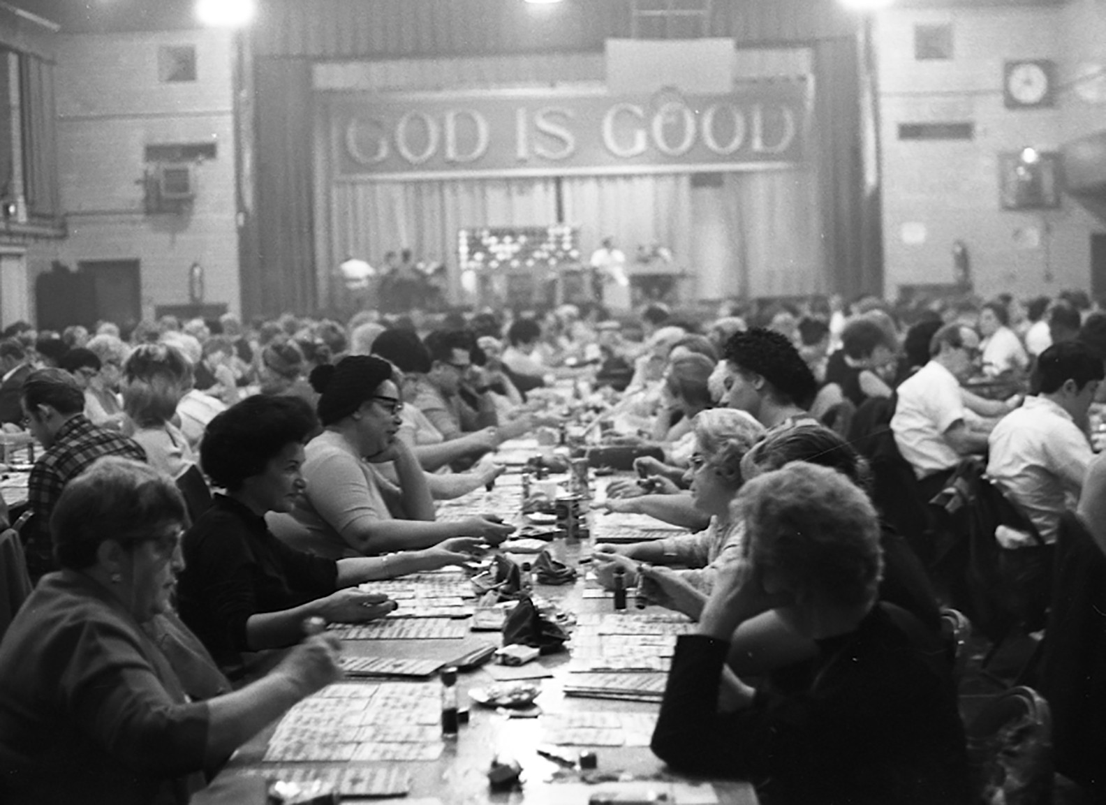 "Rows of adults sitting at tables gathered in a large auditorium space playing bingo. A large sign reading ""God is Good"" hangs above the stage."