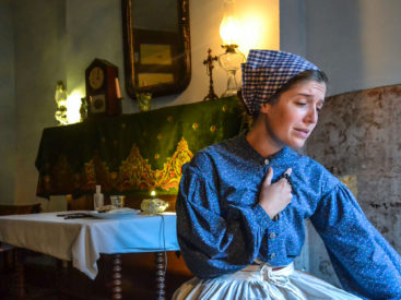 Actor playing the role of Bridget Moore inside their recreated 1896 parlor