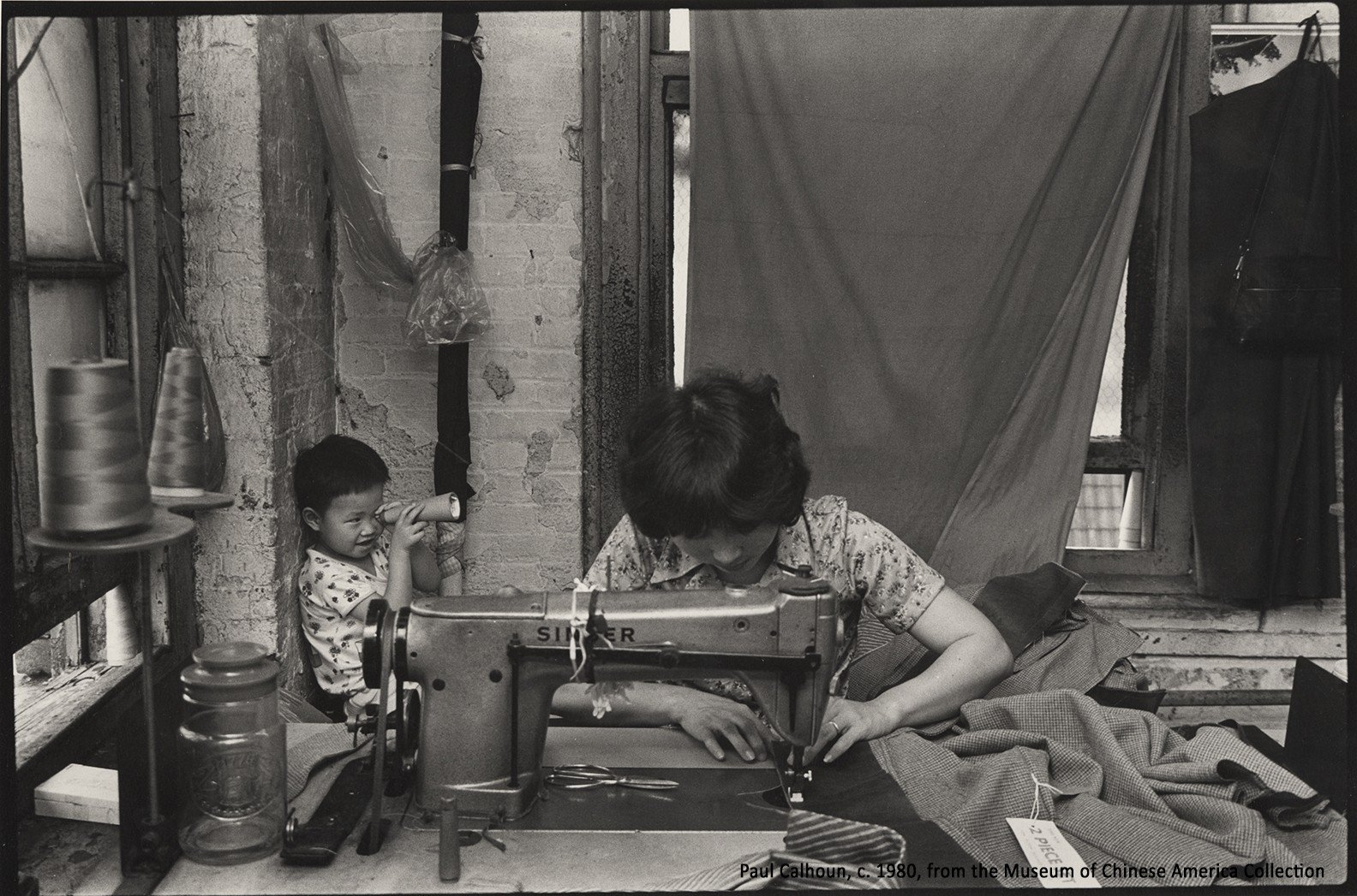 Black and white photo of a seamstress working at a sewing machine station while a young child plays in the background