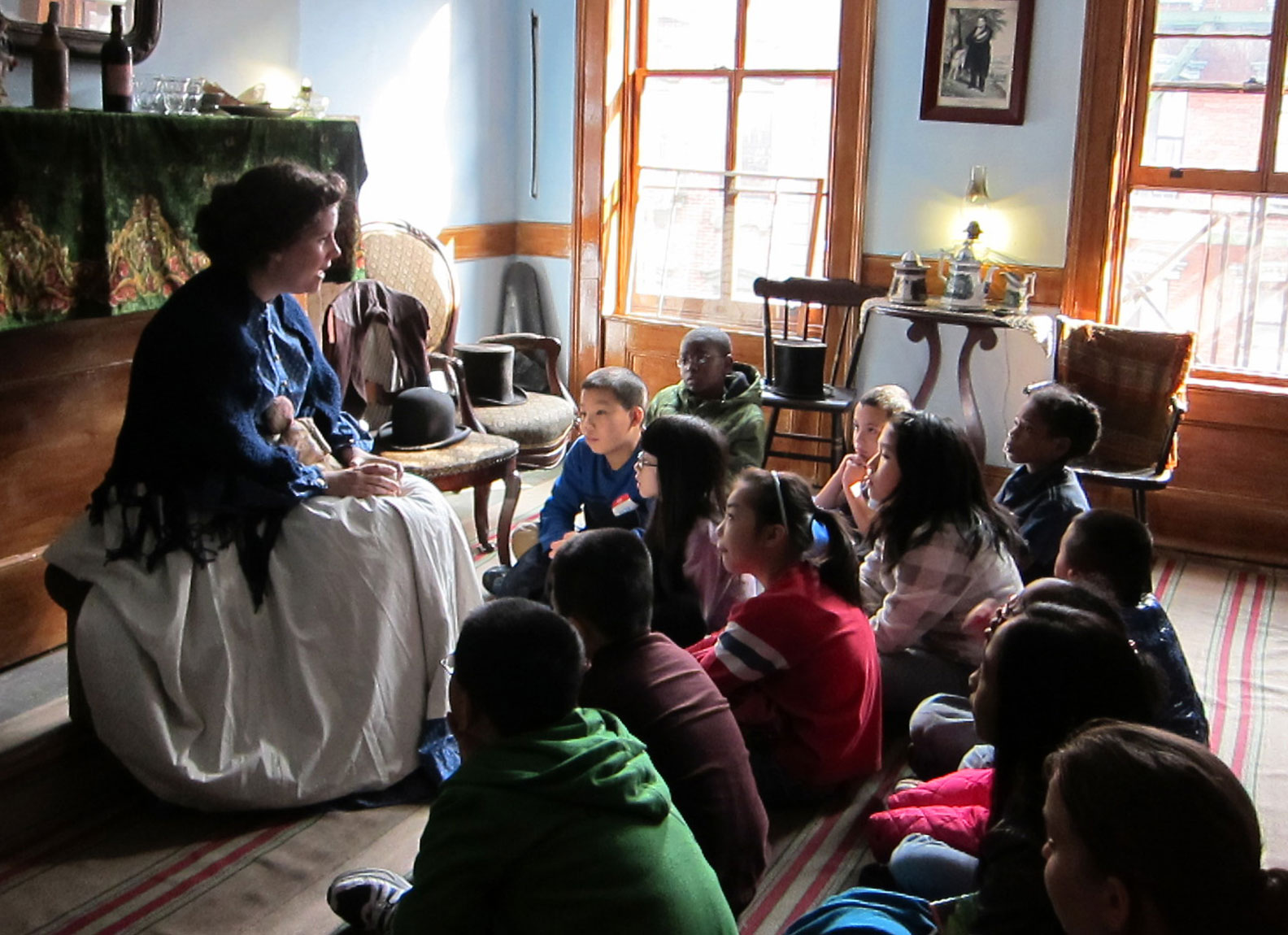 An actor in the role of Irish Immigrant Bridget Moore speaking with a group of schoolchildren.
