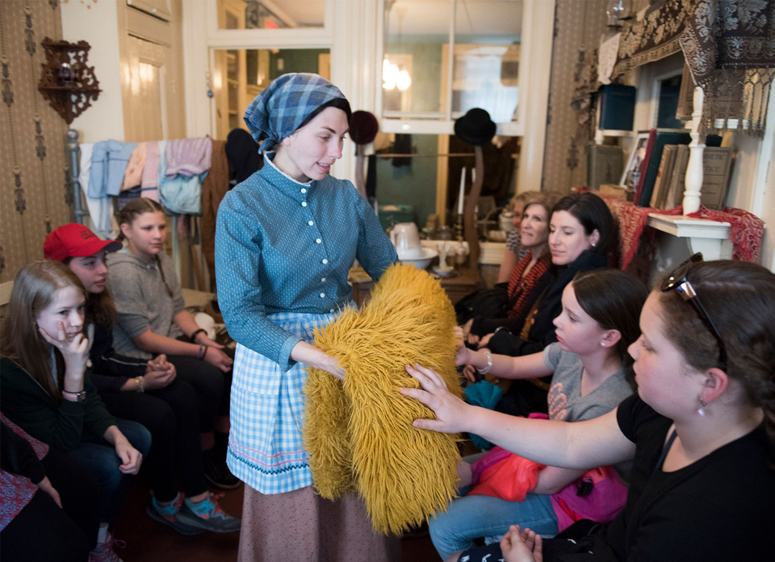 A costumed actor playing Victoria Confino interacts with students inside the family home at 97 Orchard Street.