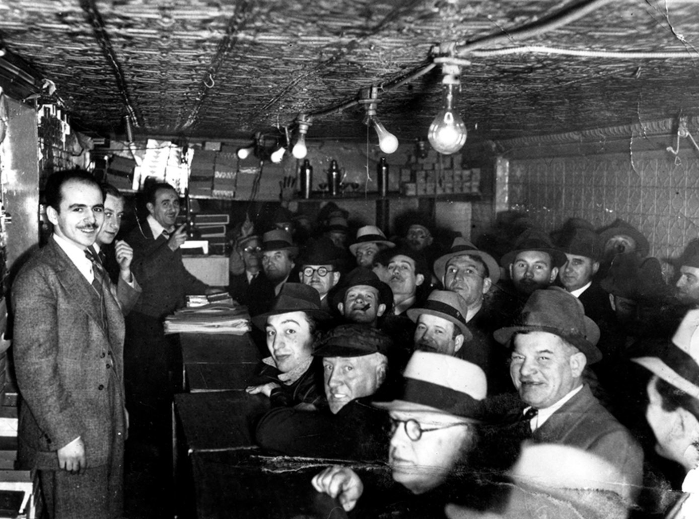 Black and white photo of Max Marcus' auction house. The space is small and crowded with adults sitting together and rows of lights hanging low above
