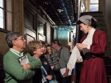 Group of Museum visitors interacting with a costumed actor playing the role of a former 97 Orchard resident