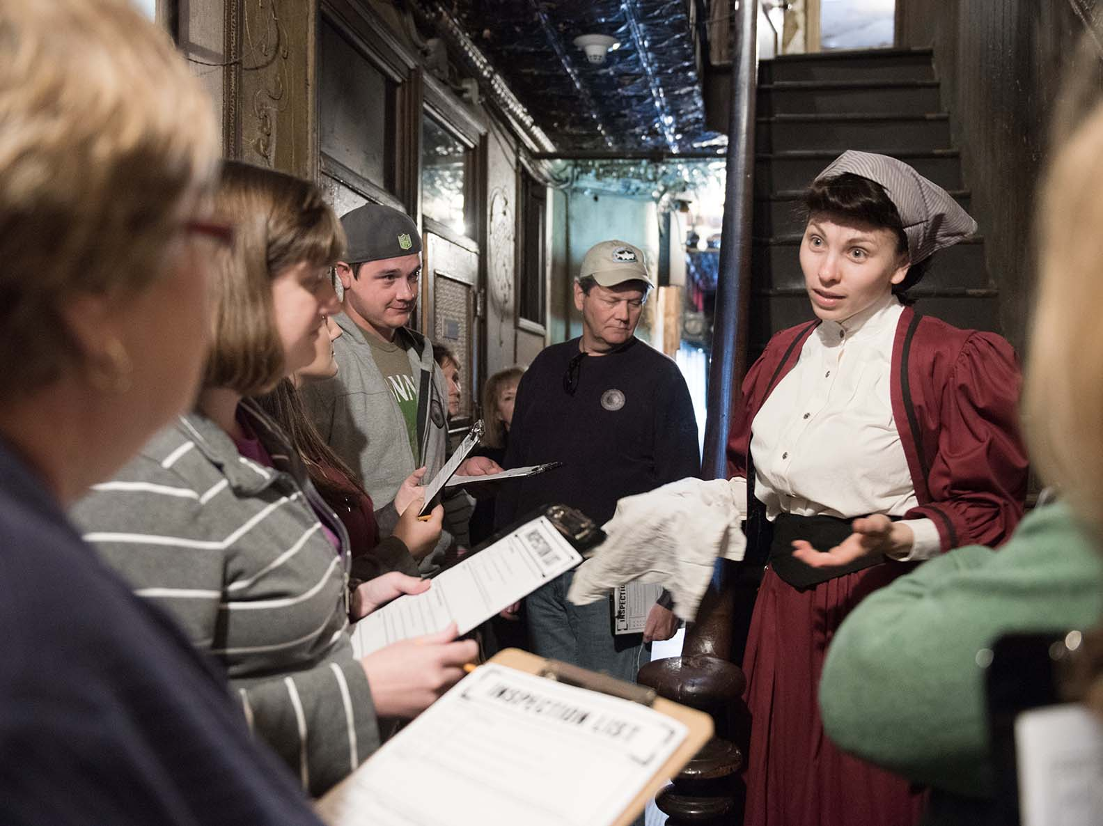 Museum visitors interacting with a costumed actor playing the role of a former 97 Orchard resident