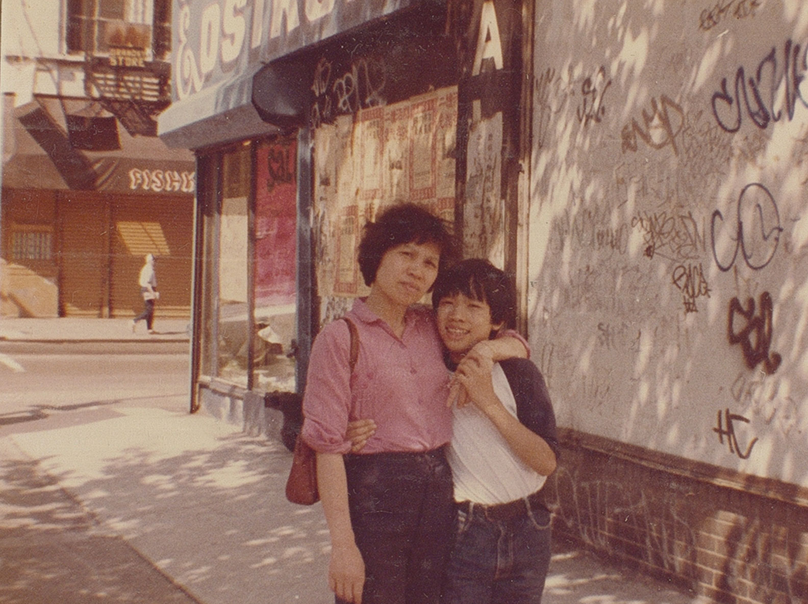 Photo portrait of Mrs. Wong and her son standing on the street in front of 103 Orchard Street