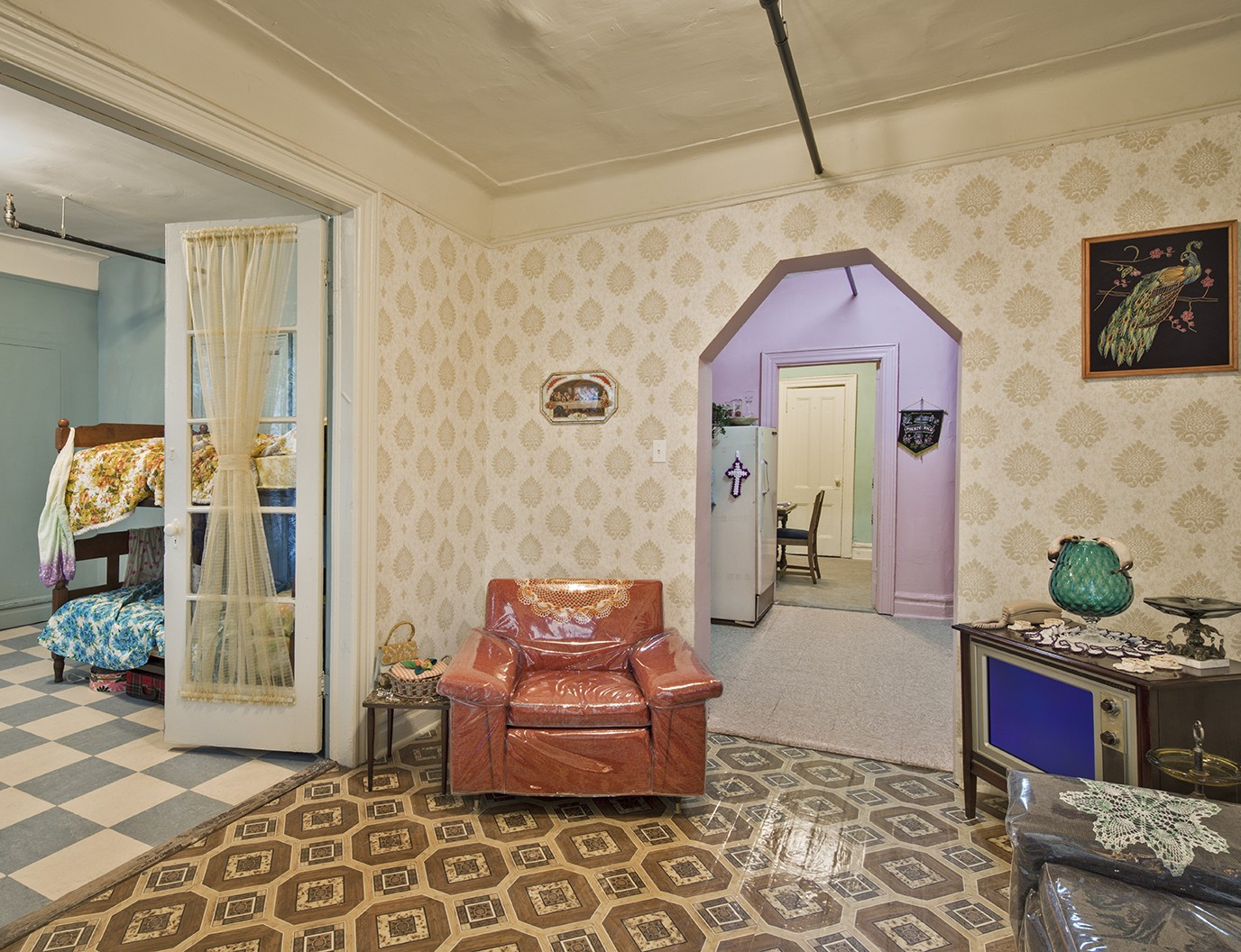 Zoomed out view of a colorful bedroom, living room and kitchen in the recreated Saez-Velez apartment at 103 Orchard Street
