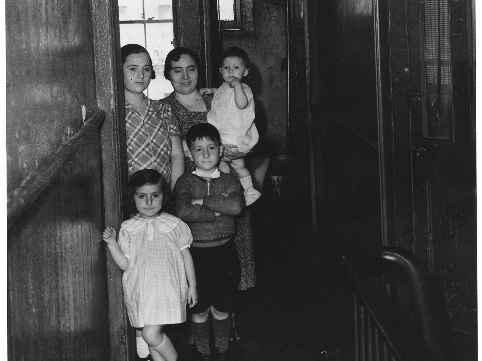 Adult carrying a baby while standing beside an older child and 2 younger children in a doorway in the hallway of a tenement