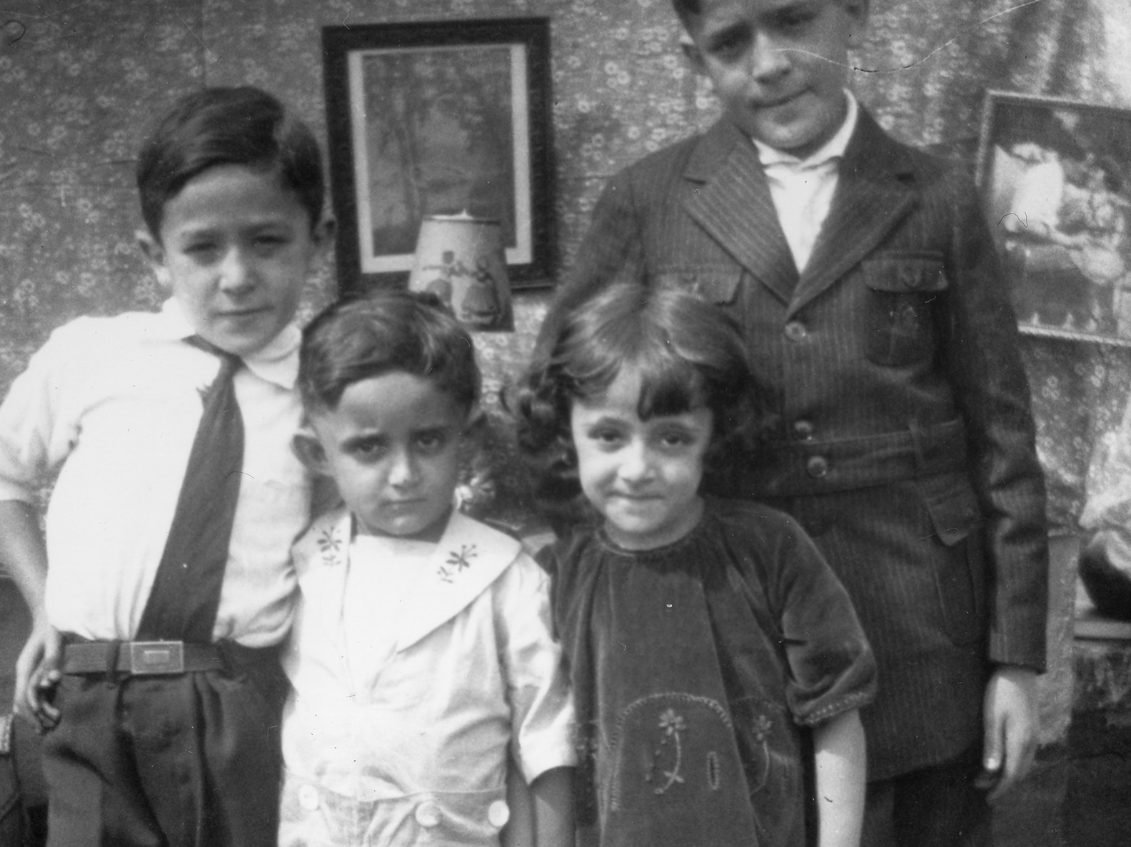Black and white photo of four children, two older and two younger, inside an apartment posing together in dress clothes