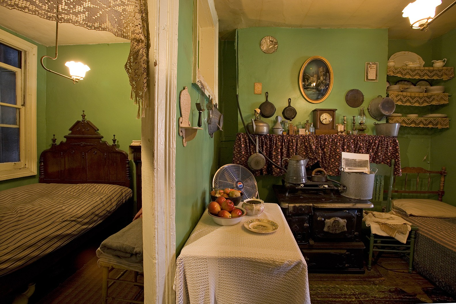 A split view of the recreated 1908 bedroom and kitchen of the Rogarshevsky family