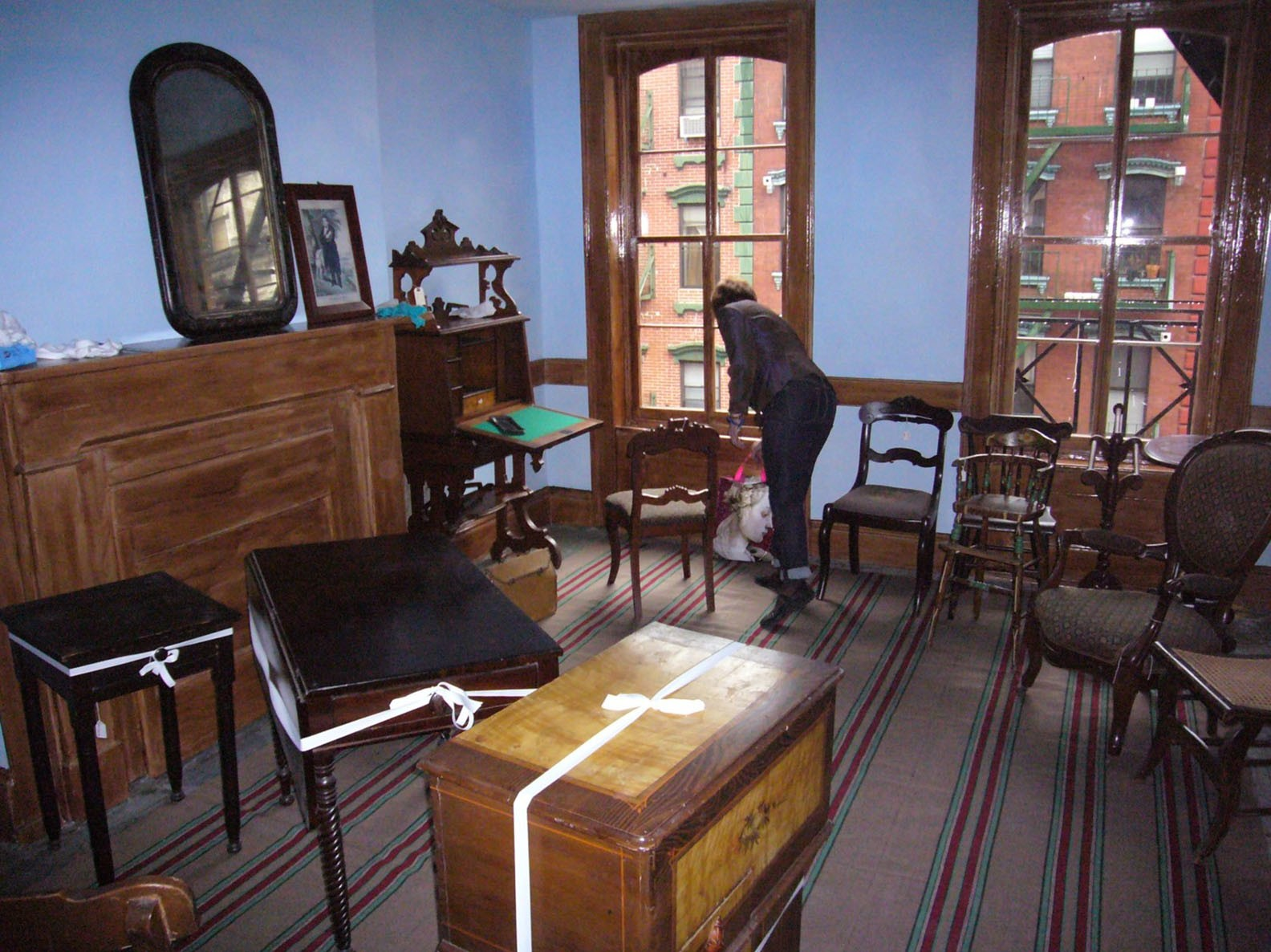 A behind-the-scenes progress shot of furniture and artifacts being set up for an apartment exhibit