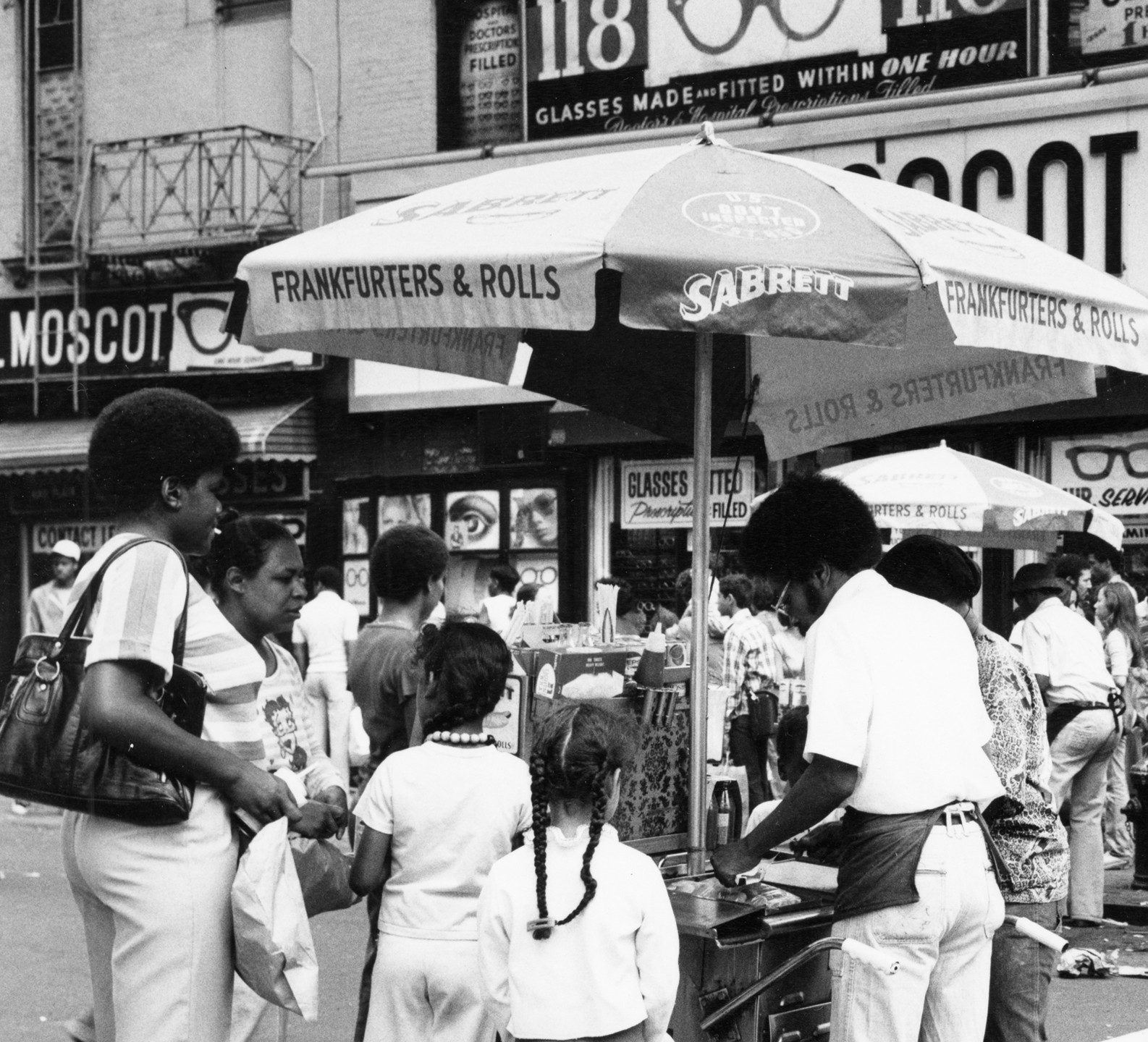 """Black and white photo of 2 children and 2 adults ordering food at a """"Sabrett"""" hot dog stand"""