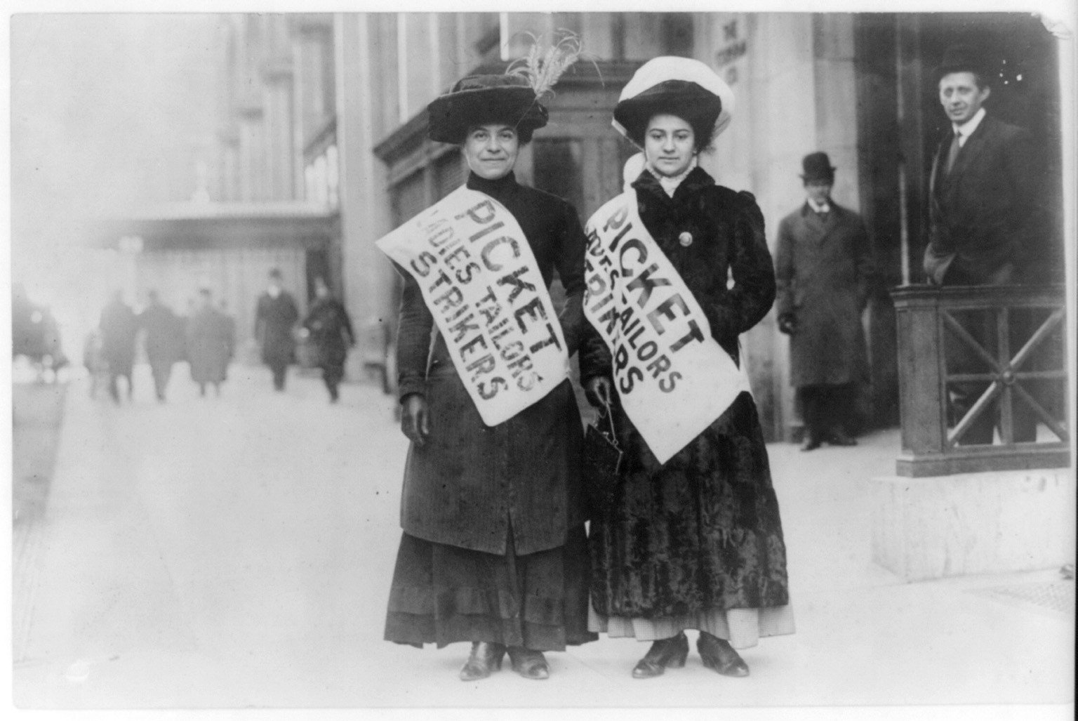 Two women picketing for garment workers rights in the early 1900s.