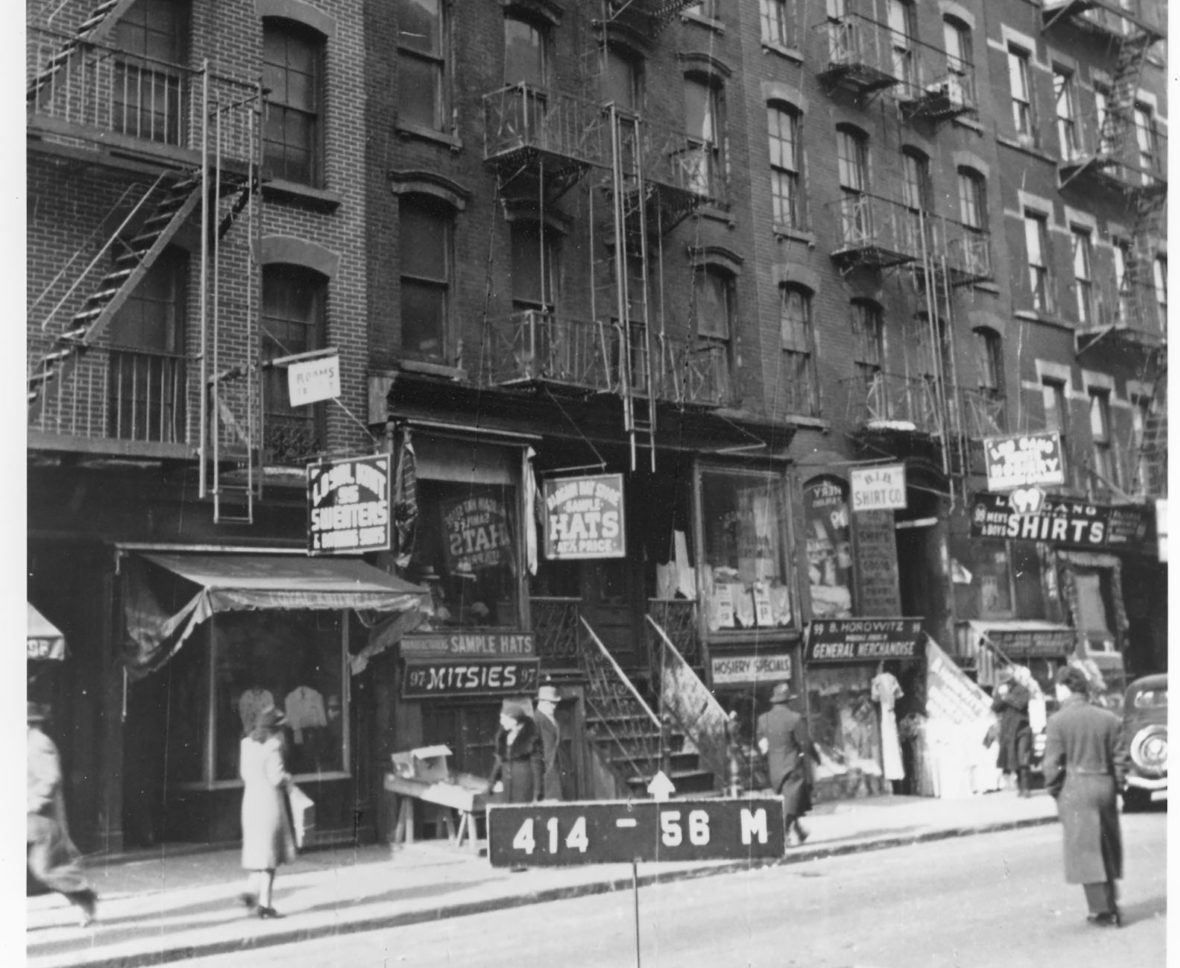A line of open shops and a few people passing by in front of 97 Orchard Street in 1940