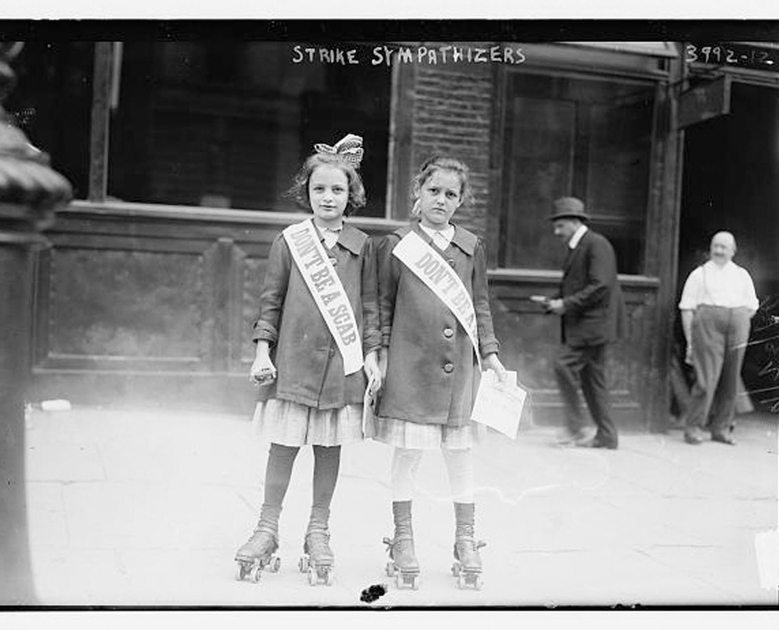 """Two young girls side by side in roller skates and matching jackets and skirts wear sashes that say """"Don't be a scab"""""""