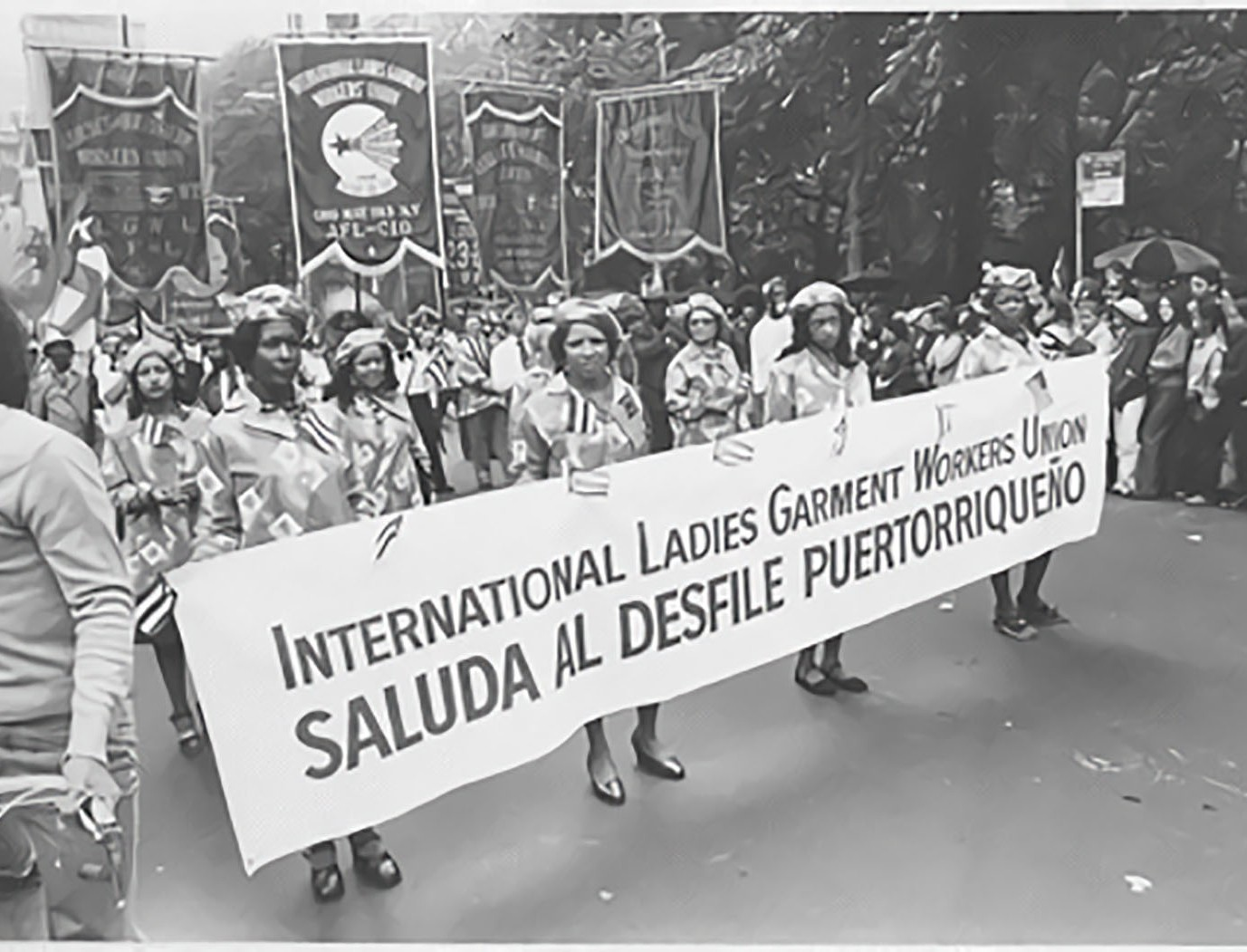 """A group of women participating in a march with a banner that says """"International Ladies Garment Workers Union Saluda al desfile Puertorriqueño."""""""