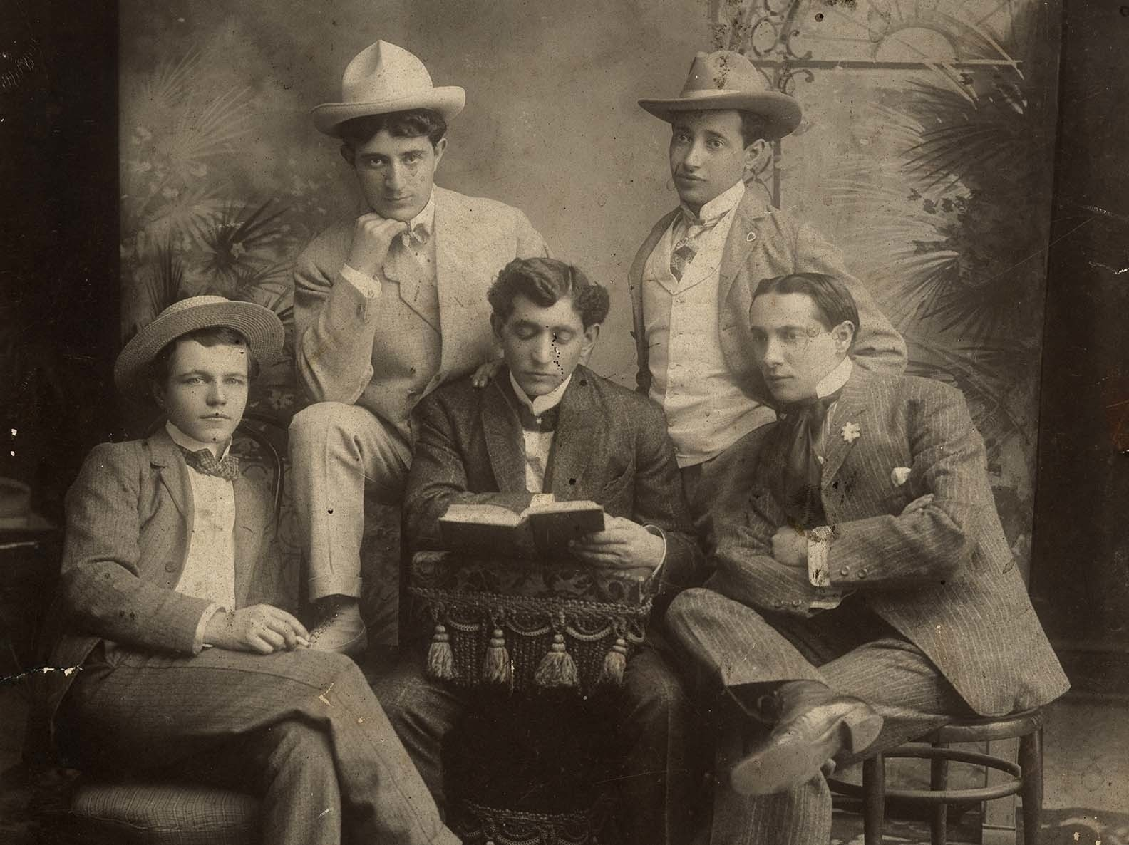 Jacob Barinescu seated in a row of three adults with two more standing behind, all in various poses dressed in suits and finery