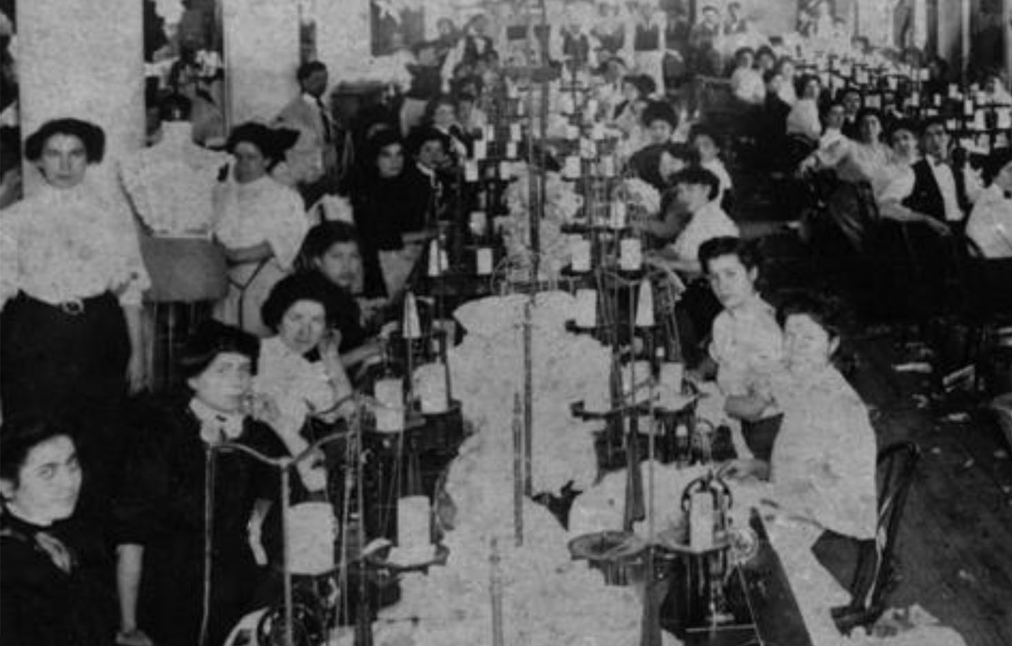 2 very long tables of female garment workers seated at various sewing machine stations at a factory