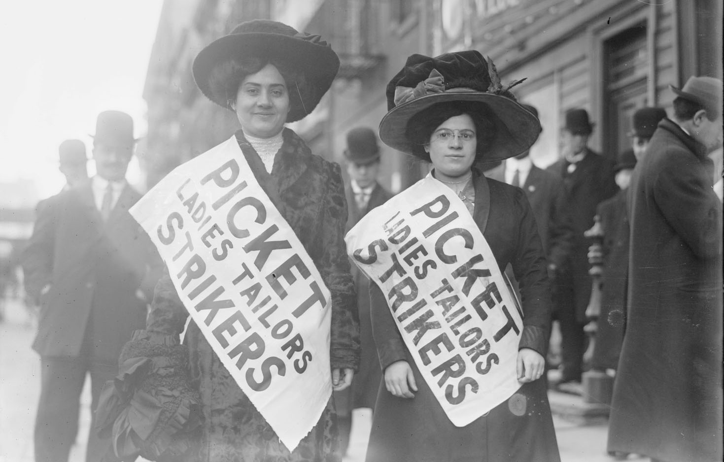 "Two adult women standing on a busy sidewalk wearing formal hats, dresses, and large sashes that read ""Picket Ladies Tailors Strikers"""