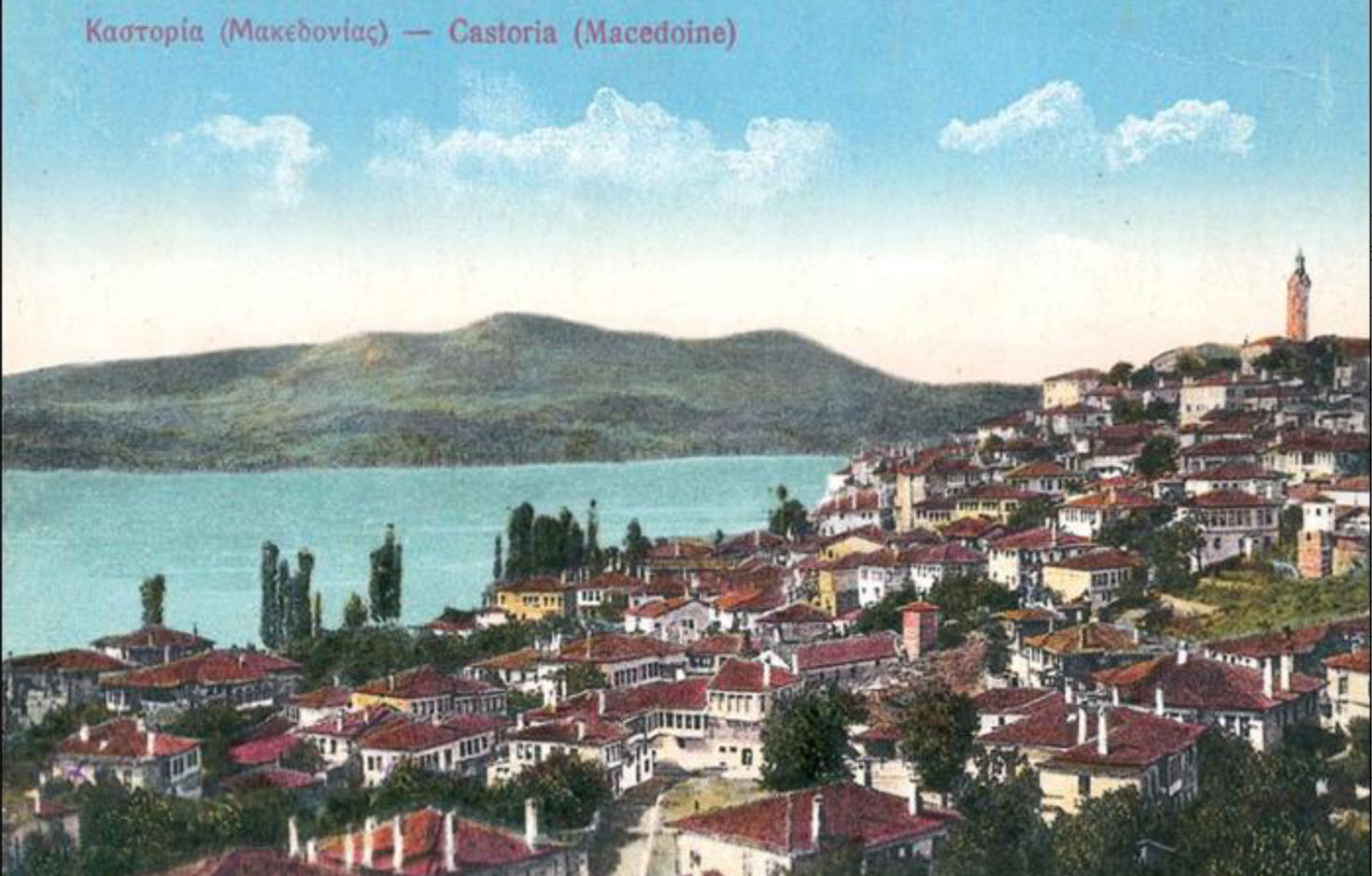 Bird's eye view of Kastoria, Greece in the 1900s - a sprawling coastal town full of trees and red-tile rooftops under a clear blue sky