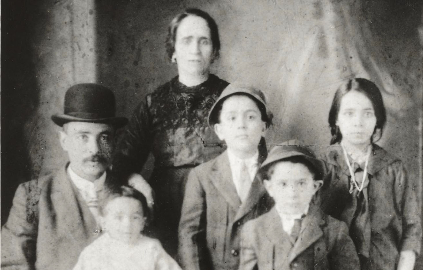 A formal black and white portrait of 6 members of the Confino family, 2 adults, a baby, and 3 other children