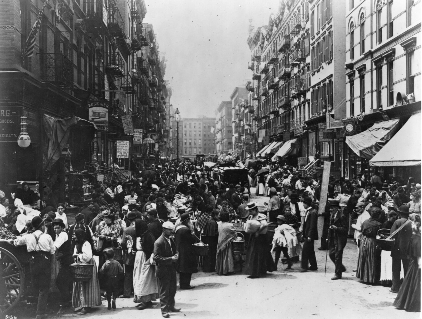 1898 photo of Orchard Street full of people crowding in the road between rows of apartment buildings and businesses