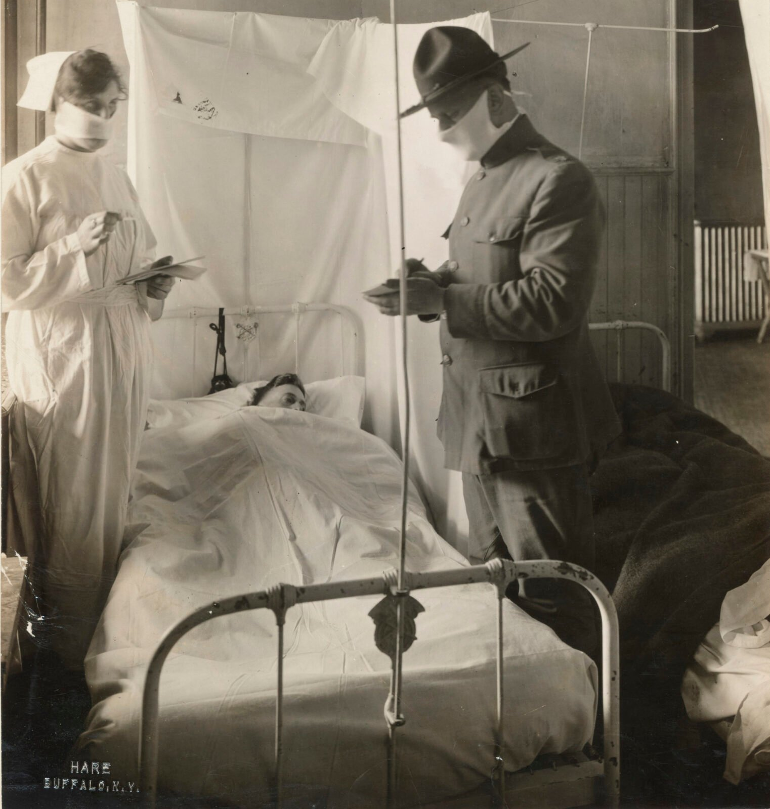 A nurse and a military officer wearing face masks take notes will standing on opposite sides of a flu patient's hospital bed