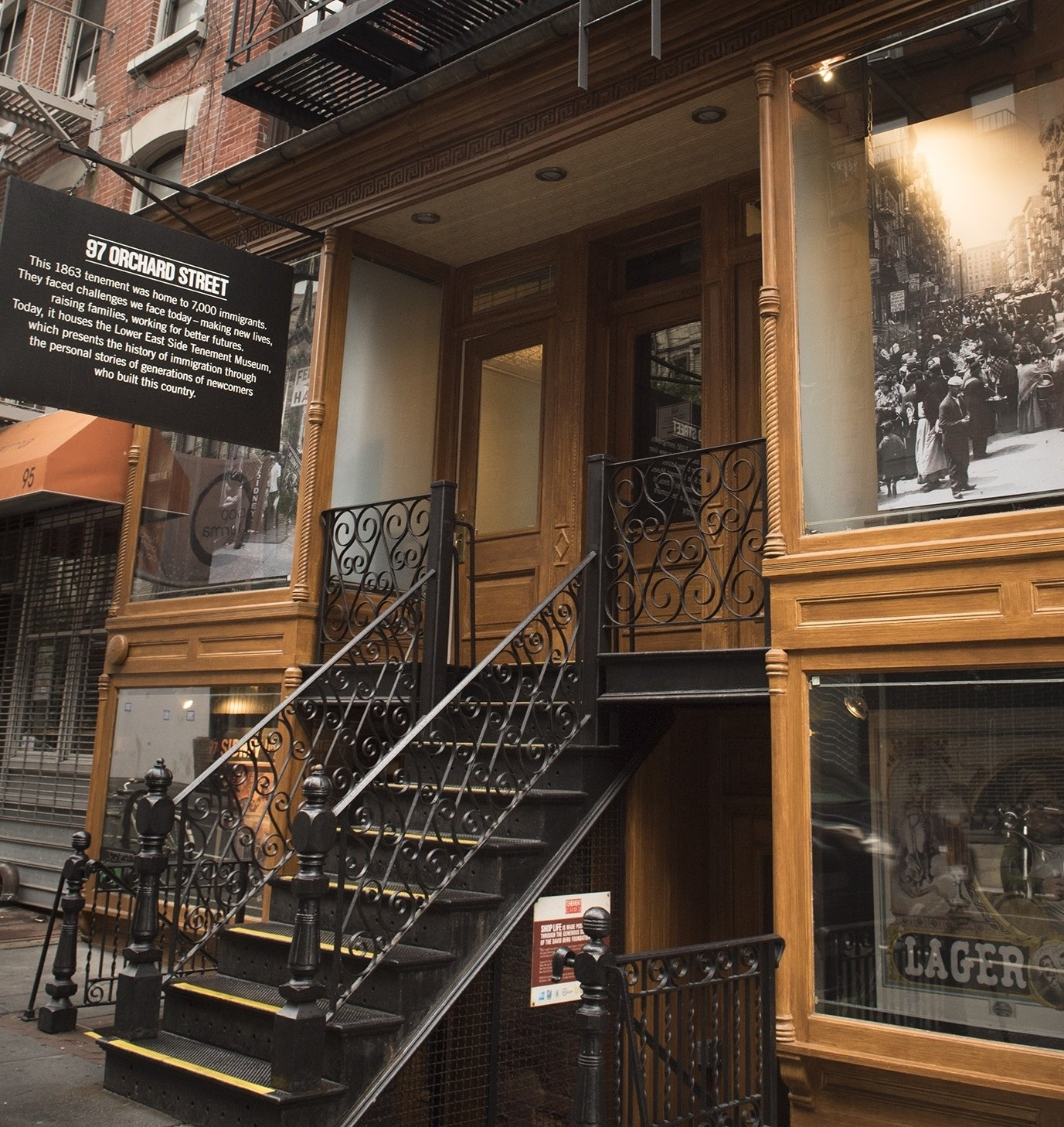 A black placard describing the history of the Museum building hangs above black steps leading up to the doors of 97 Orchard Street