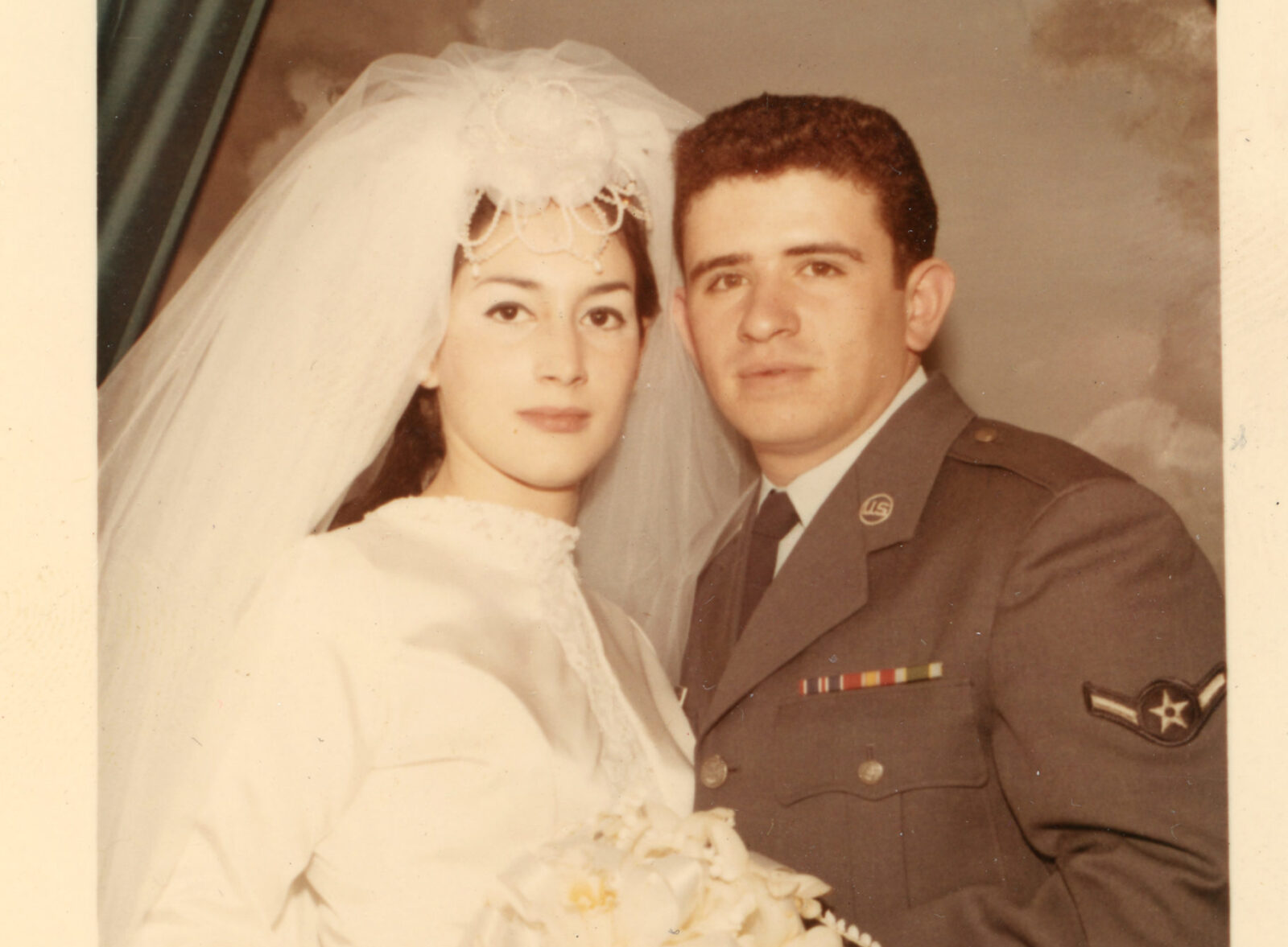 A woman with a light skin tone and dark hair in a long wedding veil and dress poses with a man with medium-light skin in a gray military uniform