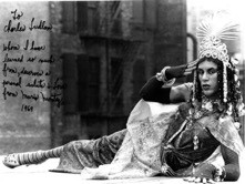 Black and white photo of a person in drag wearing an elaborate headpiece, layered dress, jewelry, and makeup posing in a reclined position outdoors
