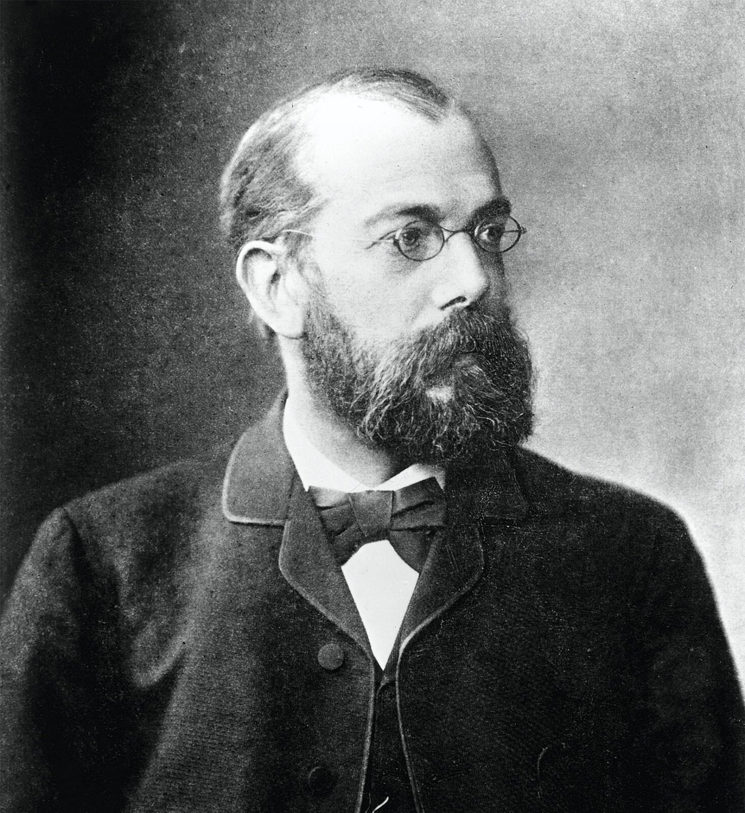 Black and white portrait of a middle-aged bearded man with a light skin tone wearing small wireframe glasses and a suit with a bowtie