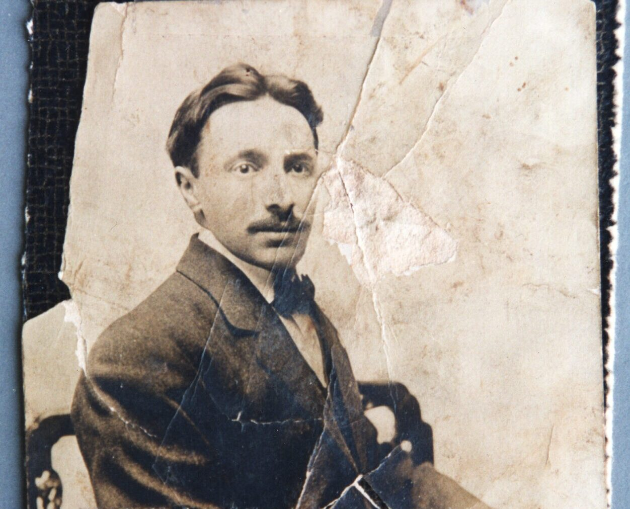 Old, weathered photo of an adult man with a light skin tone with his hair in a middle-part, a mustache, a bowtie and suit, and an open yet neutral expression