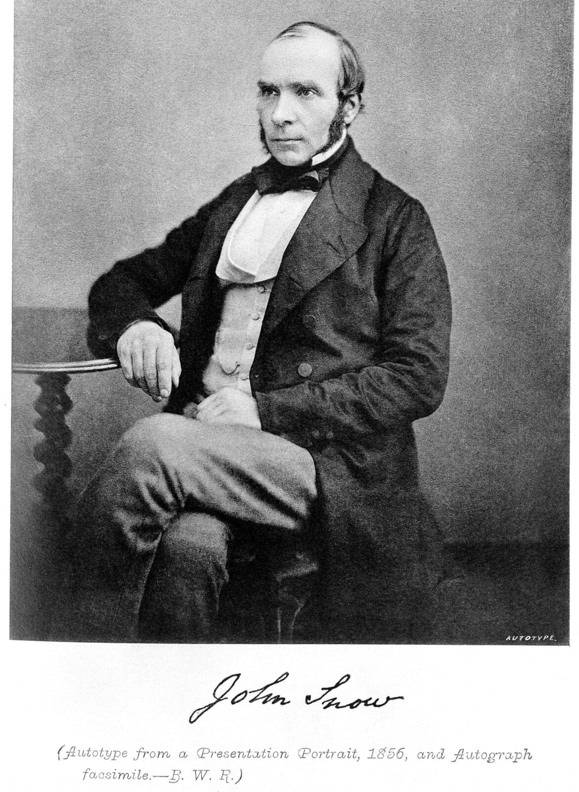 Black and white portrait of a middle-aged man with a light skin tone dressed in formal wear seated with a neutral expression looking off to the left