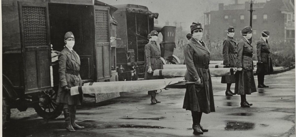 Four teams of 2 nurses wearing winter coats and  face masks stand holding empty hospital stretchers beside ambulances outside on a rainy day