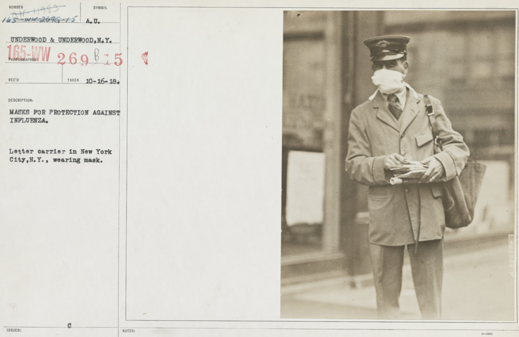 Black and white photo of a New York City postman delivering mail while wearing a face mask during the 1918 influenza outbreak